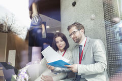 Affärsfolk som läser dokumentet, medan sitta i konventcentrum Arkivbild