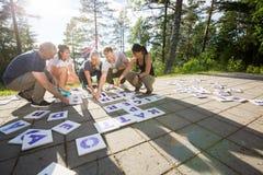 Affärsfolk som löser korsordet på uteplats i skog Royaltyfri Foto