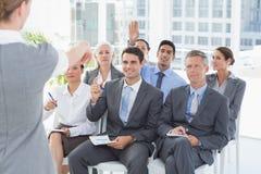 Affärsfolk som lyssnar under meting Arkivfoton