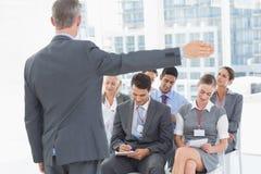 Affärsfolk som lyssnar under meting Arkivbilder
