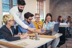 Affärsfolk som möter för att diskutera idéer i modernt kontor arkivbild