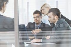 Affärsfolk som möter i styrelse bak exponeringsglas Arkivbilder