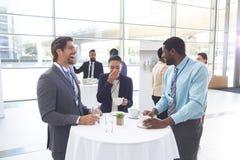 Affärsfolk som påverkar varandra med de på tabellen under ett seminarium royaltyfria bilder