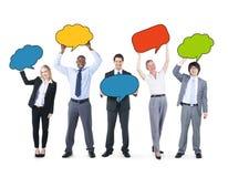 Affärsfolk som rymmer färgrika anförandebubblor Arkivfoton
