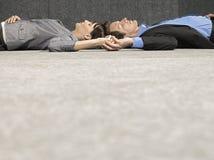 Affärsfolk som rymmer händer, medan ligga på jordning Royaltyfria Foton