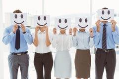 Affärsfolk som rymmer lyckliga smileys på framsidor Royaltyfri Bild