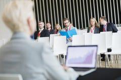 Affärsfolk som sitter i seminariumkorridor arkivbild