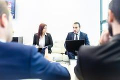 Affärsfolk som sitter på det funktionsdugliga mötet i modernt företags kontor Fotografering för Bildbyråer