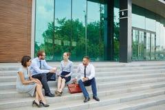 Affärsfolk som sitter på moment av kontorsbyggnad Arkivfoton