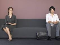 Affärsfolk som sitter på Sofa In Waiting Room arkivbild