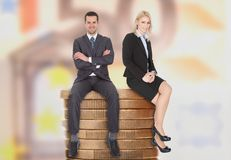 Affärsfolk som sitter på staplade mynt Arkivbild