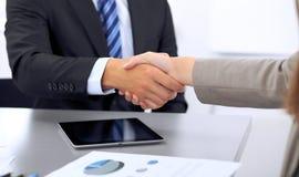 Affärsfolk som skakar händer, fulländande övre ett möte Arkivfoto