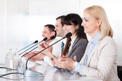 Affärsfolk som talar i mikrofon Royaltyfri Fotografi