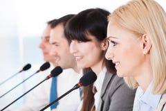 Affärsfolk som talar i mikrofon Arkivbilder