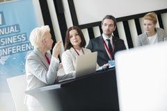 Affärsfolk som talar, medan sitta på skrivbordet i seminariumkorridor Fotografering för Bildbyråer
