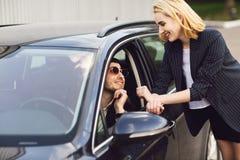 Affärsfolk som talar nära parkeringshus Mannen i exponeringsglasen sitter i bilen, kvinnan står bredvid honom arkivfoto