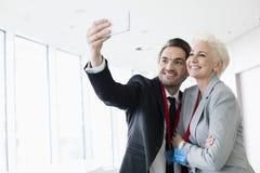 Affärsfolk som tar selfie i konventcentrum Fotografering för Bildbyråer