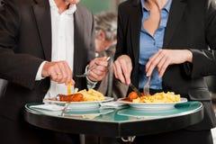 Affärsfolk som tillsammans äter läcker mat Arkivfoton