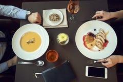 Affärsfolk som tillsammans äter middag begrepp, grillad grisköttfläskkarré med granatäpplesouce och potatis och krämsoppa royaltyfri fotografi