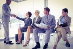 Affärsfolk som väntar för att kallas in i intervju Arkivbild