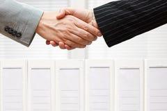 Affärsfolket är handshaking över limbindningar, affären och accouen Arkivfoto