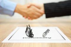 Affärsfolket är handshaking över undertecknad överenskommelse, fokus på Arkivfoton