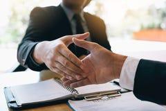 Affärsfolket accepterar eller bekräftar projekt på förslaget och sammanfogar att skaka händer på kontoret arkivfoton