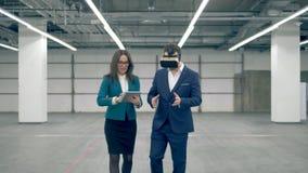 Affärsfolket använder VR-apparater, medan gå i ett kontorsrum lager videofilmer