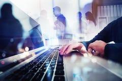 Affärsfolket arbetar tillsammans i regeringsställning med bärbara datorn i förgrunden Begrepp av teamwork och partnerskap double royaltyfri bild
