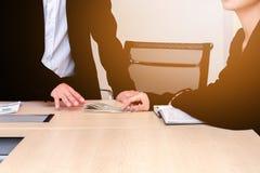 Affärsfolket ger pengar i regeringsställning arkivfoton