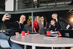 Affärsfolket i smarta tillfälliga kläder diskuterar angelägenheter, använder en bärbar dator, dricker kaffe och ler stundframstäl arkivfoton