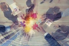 Affärsfolket sammanfogar pusselstycken i regeringsställning Begrepp av teamwork och partnerskap dubbel exponering arkivfoto