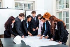 Affärsfolket som diskuterar arkitekturplan, skissar Royaltyfri Bild
