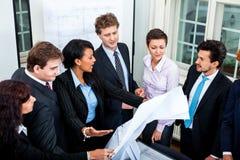 Affärsfolket som diskuterar arkitekturplan, skissar Arkivbild