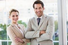 Affärsfolket som poserar med armar, korsade att le på kameran Arkivbild