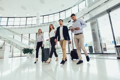 Affärsfolket talar och går samman med den digitalt minnestavlaminnestavlan och bagage arkivfoton
