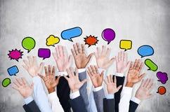 Affärsfolks armar som lyfts med anförandebubblan Arkivfoto
