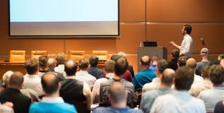 Affärshögtalare som ger ett samtal i konferenskorridor Arkivfoto