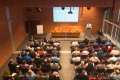 Affärshögtalare som ger ett samtal i konferenskorridor Arkivbild