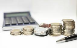 Affärsidé av billånet, den gråa bilen och buntar av mynt royaltyfri bild