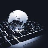 affärsidé av det glass jordklotet på ett bärbar datortangentbord Royaltyfri Foto