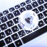 affärsidé av det glass jordklotet på ett bärbar datortangentbord Royaltyfri Bild