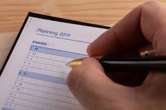 Affärsidé - den bästa sikten av en manlig hand med pennan skriver plan för det nästa året i en öppen dagbok med ordet 2019 arkivfoton