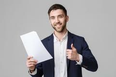 Affärsidé - för affärsman för stående stilig hållande vit rapport med den säkra le framsidan och duns upp Vit bakgrund arkivfoton