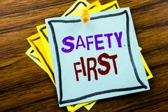 Affärsidé för säkerhet för handstiltextvisning första för säker varning som är skriftlig på klibbigt anmärkningspapper på träbakg Arkivbild