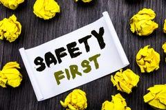 Affärsidé för säkerhet för handstiltextvisning första för säker varning som är skriftlig på träbaksida för klibbig för anmärkning Royaltyfri Bild