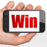 Affärsidé: Hand som rymmer Smartphone med seger på skärm Arkivbilder