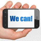 Affärsidé: Handen som rymmer Smartphone med kan vi! på skärm Arkivbild