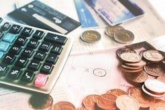 Affärsidé med mynt, stopptidkalender, räknemaskin, kreditkort arkivbild