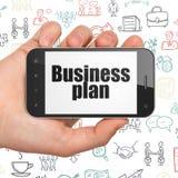 Affärsidé: Räcka hållande Smartphone med affärsplan på skärm Arkivbild